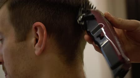 shaves : Barber cuts a man with a hair clipper close-up.