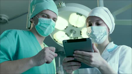 cerrahi : Surgeon is reading a patients case history and giving his instructions to the nurse. Young nurse is standing by him and writing the directions down with her tablet PC. alexa