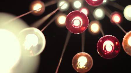 вешать : Low-angle shot of many little shining bulbs in multicolored lampshades. Camera is moving around.