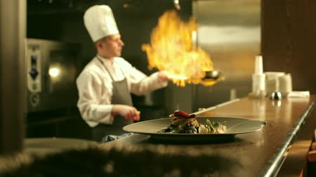 chef cooking : Male chef is cooking flambe meat in restaurant kitchen. Ready-to-eat dish is standing on the counter in the foreground.