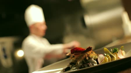 chef cooking : Table-ready meat dish is standing on the counter in the foreground. In the background chef is cooking flambe meat. Stock Footage