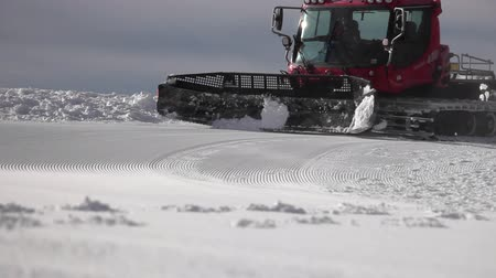 snowcat : Low-angle shot of a mountain ski piste. Snowcat is moving along grooming it before the competition. Stock Footage