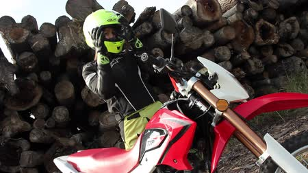 autobike : Female biker is taking on the helmet, getting on the motorcycle, starting the engine and going off.