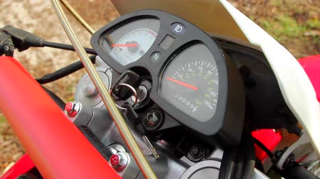 autobike : Closeup shot of a dashboard of the motorcycle. Biker is putting key into ignition switch. Stock Footage