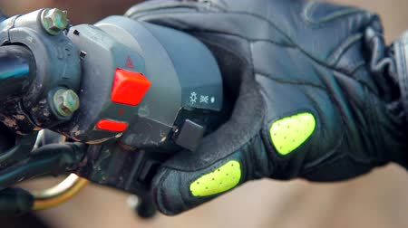 lovas : Closeup shot of a right grip of a motorcycle. Biker is pressing start button and bending the throttle.