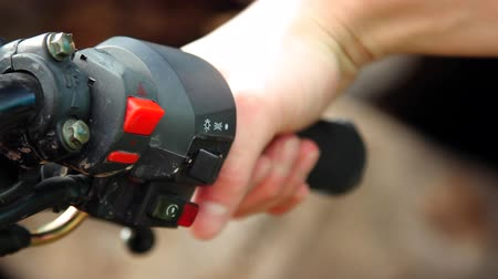 autobike : Closeup shot of a bikers hand pressing the motorcycle start button and moving throttle control handle.