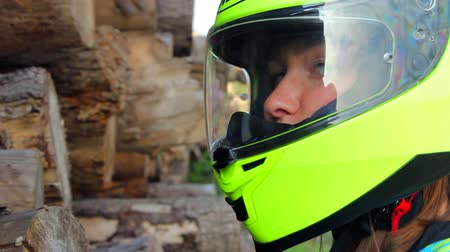 helmets : Profile of a female biker shutting the visor of motorcycle helmet and turning to the camera.