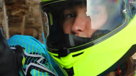 helmets : Closeup shot of a young white woman in motorcycle helmet. Shes shutting the helmets visor.