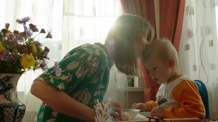 čelo : Mother and little son are sitting in the kitchen. Boy have finished the meal and mother is kissing him. Dostupné videozáznamy