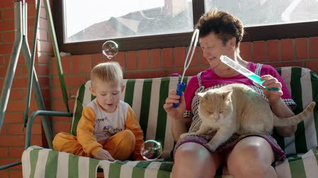 бабушка : Little boy and his grandmother are sitting on the garden swing bench. They are blowing soap bubbles and popping them.
