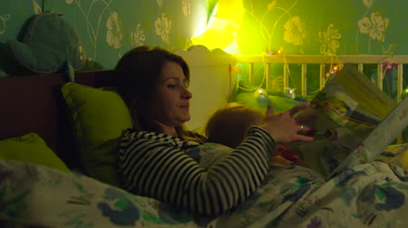 sleep : Young mother and her little son are lying in the bed and going to sleep. Mother is reading a book to the boy. Stock Footage