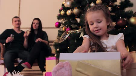 С Рождеством : Little girl is sitting by the Christmas tree and taking out her present from the gift box.