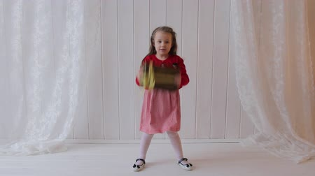 подарок : Little girl is holding gift box in hands, shaking it and jumping.