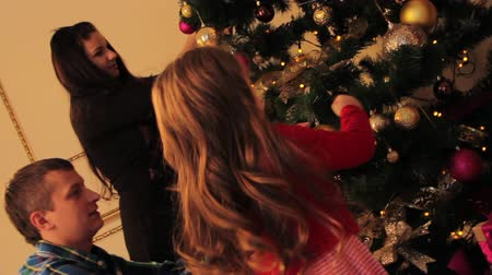 Рождественский бал : Family Decorating Christmas Tree at Home