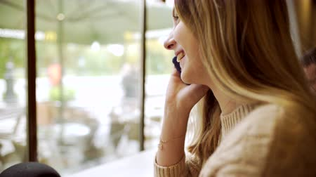 Young woman talking on the phone and smiling in coffee house Stock Footage