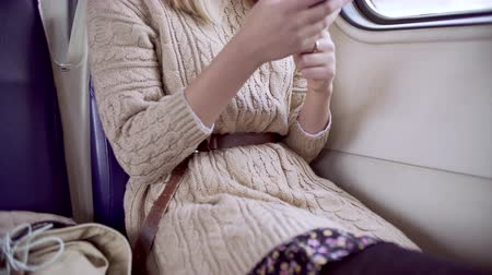 Teen girl typing message on phone sitting in electric train