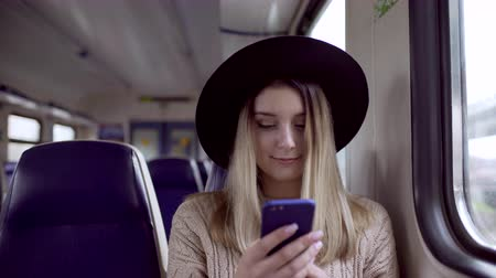 Young woman typing message on her phone and smiling, sitting in electric train