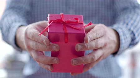 подарок : Man giving a gift in pink box with red ribbon Стоковые видеозаписи