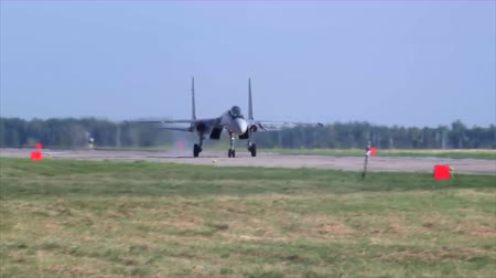 might : The russian fighter aircraft SU-35 makes a landing using parachute at a military aerodrome