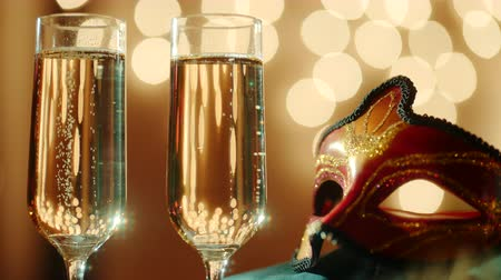 premier : Two glasses filled with bubbly champagne and carnival masquerade mask. Bokeh lights on the background