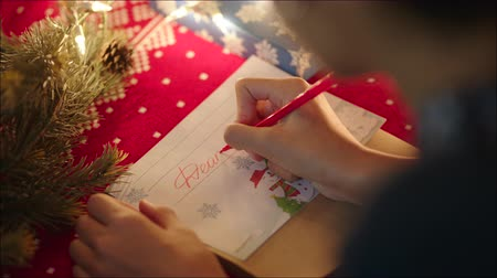 święta : Teen girl is lying near decorated christmas tree and writing christmas letter to Santa Claus on Christmas Eve