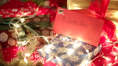 święta : A red envelope with letter to Santa Claus is lying under the Christmas tree among gift boxes and bright illumination