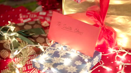 święta : Christmas letter for Santa Claus and beautiful gift boxes under the christmas tree