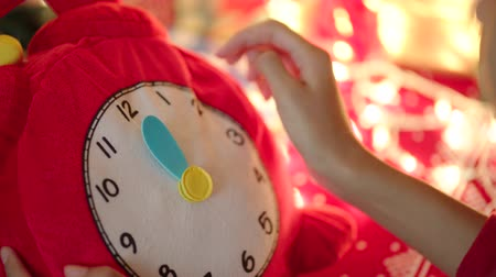 święta : Close up shot of teen girl hands translating toy clock hands to Christmas midnight Wideo