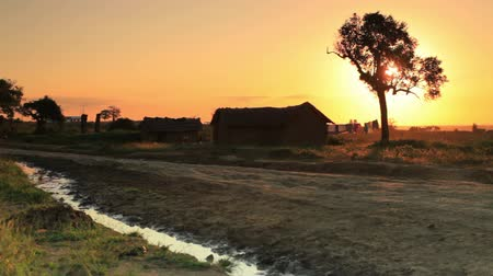 deprived : dirt road and homes at sunset