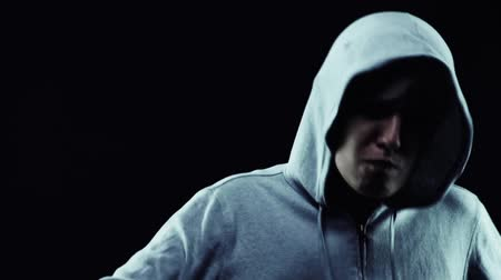 Slow motion of an angry hooded tomboy gesturing against a black background Stock Footage