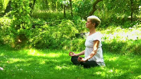Young, Blond Women Meditating In Park