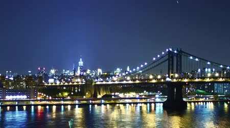mosty : New York skyline and Manhattan bridge at night. Time lapse and loopable Wideo
