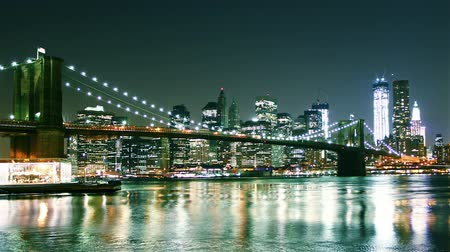 večer : Manhattan skyline and Brooklyn bridge at night. Time lapse and loopable