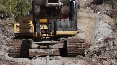 Digger on track for Man drilling holes for seismic testing, West Coast, New Zealand Stock Footage