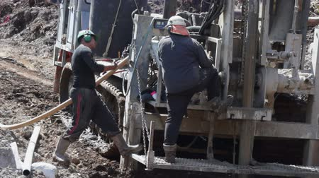Men drill holes for explosives to be used in a seismic reflective survey, December 13, 2012, near Greymouth, New Zealand