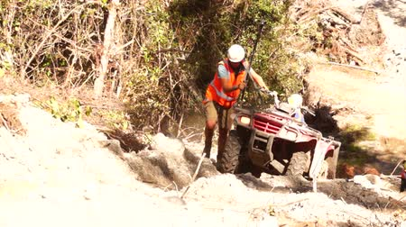 Men push a quad bike up difficult terrain while setting up for a seismic test in New Zealand