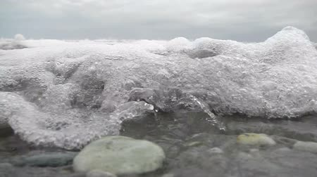 small incoming wave engulfs the camera on a West Coast beach, New Zealand Stock Footage