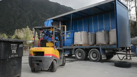 forklift unloads bins of offal at a rendering plant Stock Footage