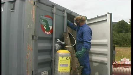 Man fumigates a 40 foot shipping container at a West Coast factory, New Zealand