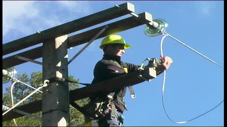Linesman attaches new wires to a power pole Stock Footage