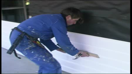 vállalkozó : A builder installs PVC wall cladding on a large building Stock mozgókép