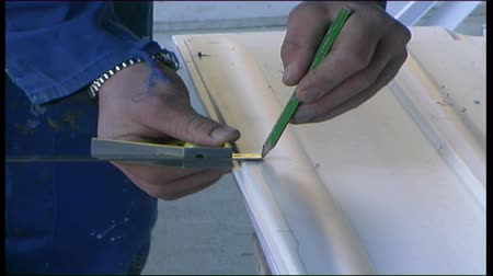 A builder installs PVC wall cladding on a large building Stock Footage