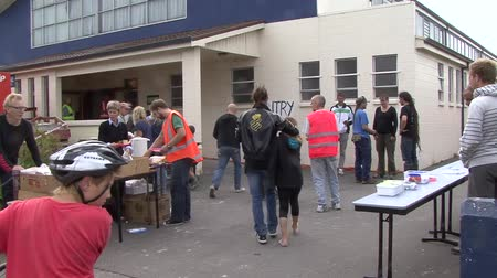 CHRISTCHURCH, NEW ZEALAND, FEBRUARY 23, 2011 - People gather outside an emergency food relief centre after a 6.4 earthquake in Christchurch, South Island, New Zealand, February 23, 2011 Stock Footage