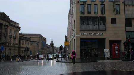 fife : August 2017: People crossing the street in front of a branch of the Royal Bank of Scotland. The day is cold and rainy. August 2017 in Edimburgh