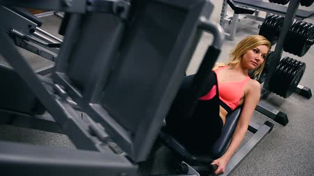 quads : Young woman working her quads at machine press in the gym. Pretty Hispanic brunette exercising in a simulator in a gym