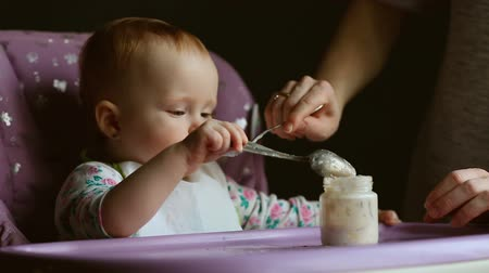 blueeyes : Cute baby sitting on a highchair while being fed against a grey background Stock Footage