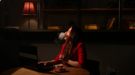 замена : Girl working with laptop drinking coffee Smoking an electronic cigarette. Working remotely in a cafe.