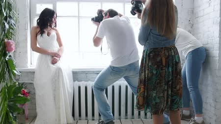 photography themes : Photographers photographing a beautiful brunette bride model. In a wedding dress in a master class. The girl is posing by the window.Photographs are trained. Stock Footage