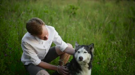 leisureactivity : Man and dog Siberian huskies concept. Asian young man with his dog on meadow.