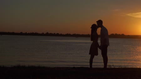contentamento : Loving senior couple enjoying a romantic sunset evening dancing together on the beach filmed Stock Footage